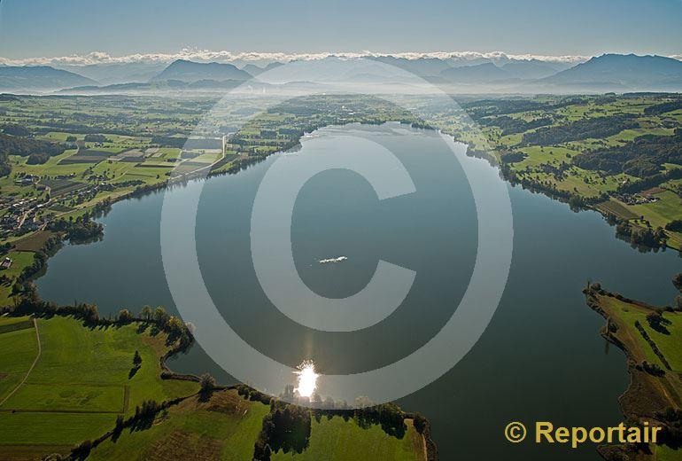 Foto: Der Baldeggersee LU glänzt in der Sonne. Im Hintergrund die Föhnwand über der Alpenkette. (Luftaufnahme von Niklaus Wächter)
