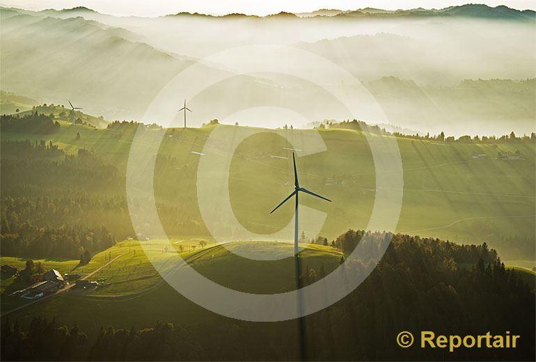 Foto: Windkraftwerke im nebligen Abendlicht der Biosphäre Entlebuch. (Luftaufnahme von Niklaus Wächter)