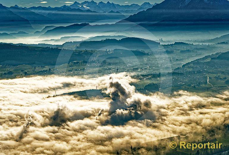 Foto: Hochnebel, Dunst und die qualmenden Kamine der Papierfabrik Perlen sorgen für eine dramatische Stimmung bei Luzern. (Luftaufnahme von Niklaus Wächter)