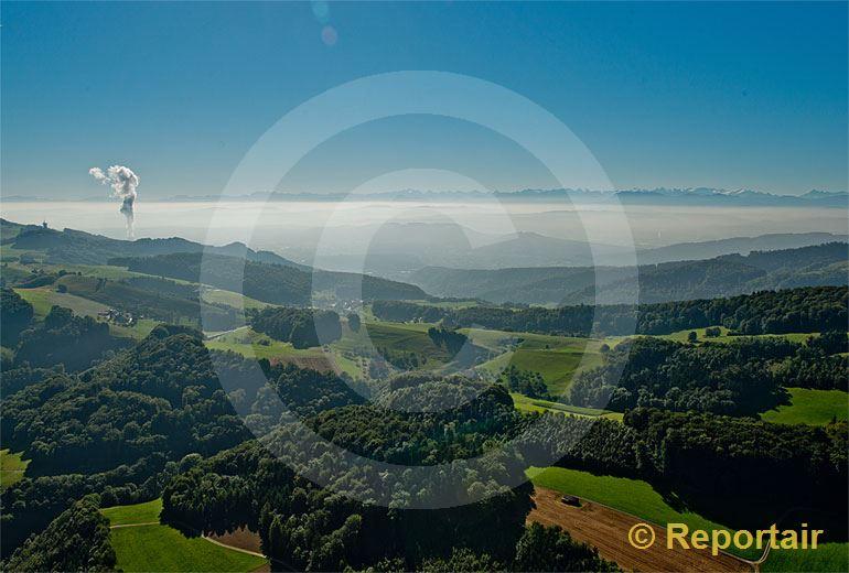 Foto: Blick von den Jurahöhen über das neblige Mittelland zu den Alpen. Links die Wasserdampffahne des Kernkraftwerks Gösgen (SO).. (Luftaufnahme von Niklaus Wächter)